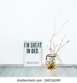 White frame with quote  I'M GREAT IN BED. I CAN SLEEP FOR DAYS. Hipster scandinavian style room interior. Jar with garland and weathered brunches. Creative lightning.