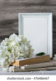 White frame for quotes with white hydrangea bouquet and books on the vintage table. Wedding decoration with text space. Frame for quotes.
