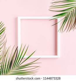 White frame and tropical palm leaves Phoenix on pink background. Flat lay, top view