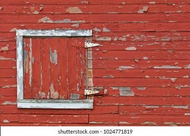 A white framed barn door with peeling paint shows on red peeling barn siding.
