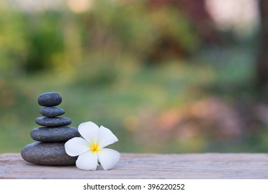 white frangipani flower and stone zen spa on wood with garden blurred background