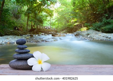 white frangipani flower and stone zen spa on wood with blurred waterfall background