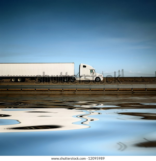 White freight truck driving on freeway under blue sky.