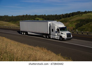 White Freightliner Cascadia pulling a white unmarked trailer along a rural Oregon Highway.  June 20th, 2017 Rural Oregon, USA