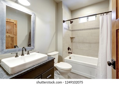 White and fresh bathroom interior with a rectangular vessel sink and ivory subway tile shower surround .