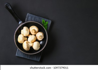 White fresh champignons with parsley on a wooden board on a gray dark table. Mushrooms. Copy the space. Top view