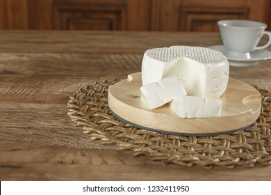White and fresh cheese, accompanied by a cup with coffee, and on wooden table - traditional products of the State of Minas Gerais - Brazil.