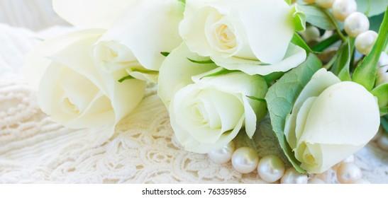 white fresh  rose flowers   on white lace background