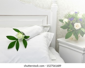 White fresh rose on a pillowon on white wooden bed covered with white linens. Bouquet of flowers on a nightstand. Selected focus on a pillow with rose on. Artistic blur of bouquet on nightstand
