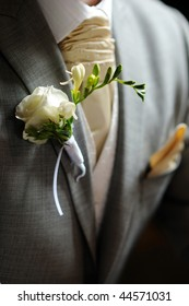 White fressia boutonniere on groom's suit