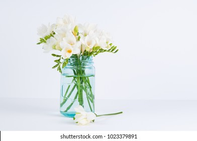white fressia flowers in a blue glass jar on a white background