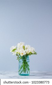 white fressia flowers in a blue jar
