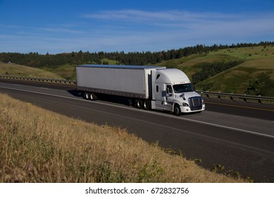 A white Frieghtliner Cascadia pulls a white unmarked trailer along a rural Oregon Highway.  June 20th, 2017 Rural Oregon, USA