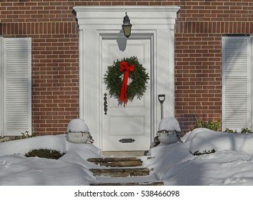 white front door with Christmas wreath on a snowy day