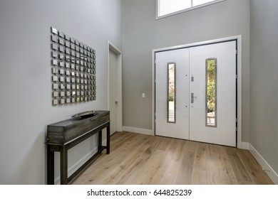White front door opens to a contemporary two story grey foyer fitted with a black console table positioned under metal mirror wall art. Northwest, USA