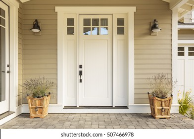 White front door with small square decorative windows and flower pots
