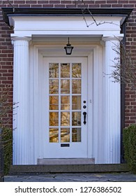 white front door with window panes and columns