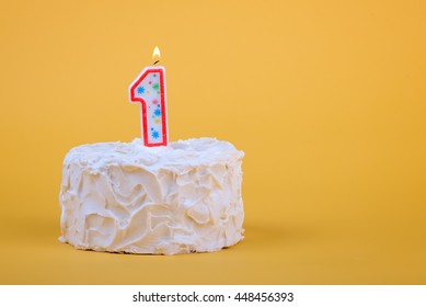 White Frosted Cake With Candle 1 Lit On Top Of It