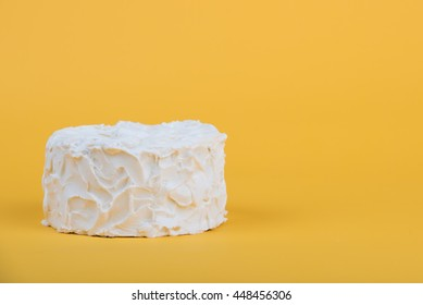 White frosted cake on yellow background