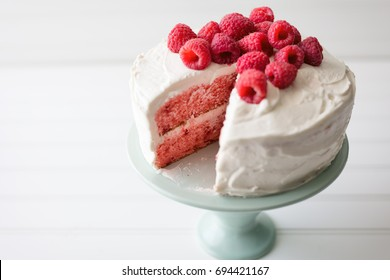 White frosted raspberry layer cake with fresh raspberry topping on an aqua blue cake plate.