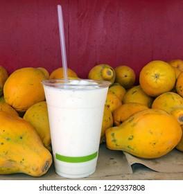 White Fruit Smoothie stands among papaya pile