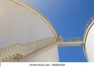 white fuel tanks against blue sky, white steel petroleum silo
