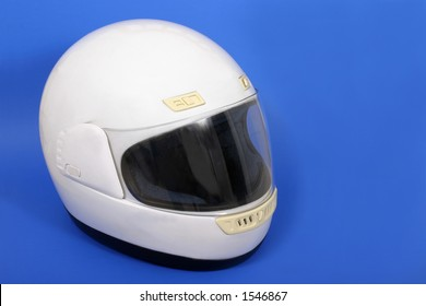 White full face motorcycle helmet on a blue background.