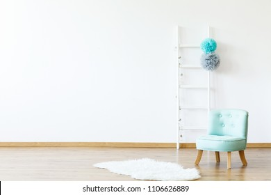 White fur next to blue chair in empty boy's room interior with copy space and ladder. Real photo