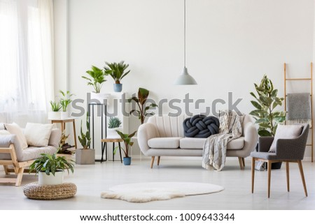 White Fur And Pouf In Bright Living Room Interior With Settee Under Grey  Lamp Near Armchair