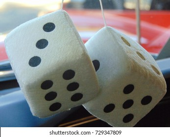 White fuzzy dice hanging from a rear view mirror of a car