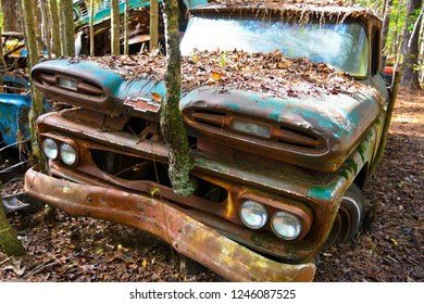 White, GA / USA - October 27, 2018 - Close-up Image of an Old Scrap Truck in a Junk Yard with Tree Growing out of the Front Grill