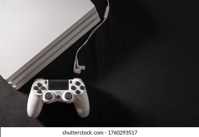 White game console with control and handset on black background