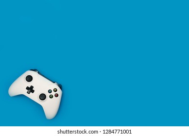 White game pad isolated on blue background. Video gaming concept.