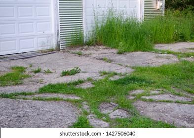 White garage door with overgrown neglected grass in cracked concrete carport driveway.  Home improvement.