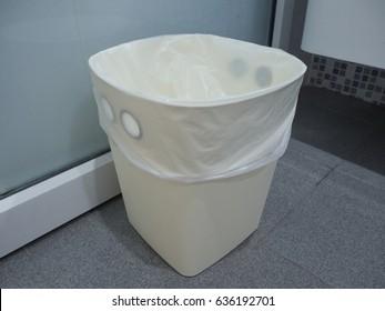 white garbage bin in the bathroom
