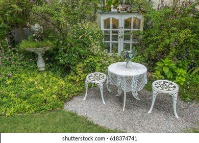 White garden chairs and table in the garden