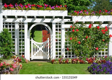White Garden Gate And Fence In Colorful Botanical Garden