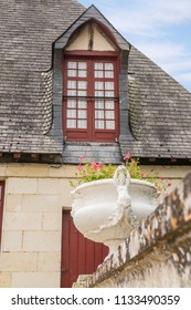 White Garden Pot with Red Flowers and House with Red Dormer Window