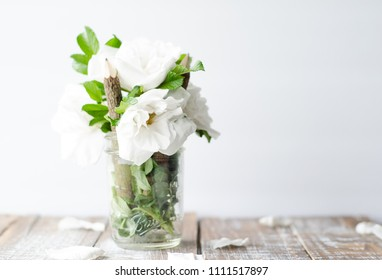 white gardenia flowers on wooden desk  in mason jar