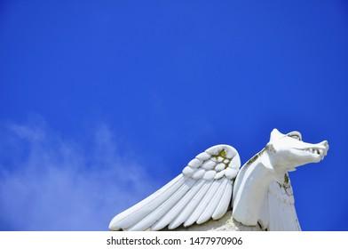 A white gargoyle against a bright blue sky.