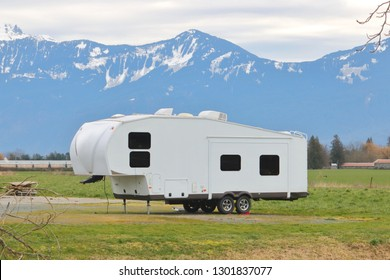 A white, generic camper setup in front of snow capped mountains.