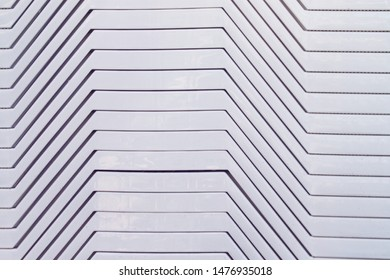 White geometric surface, folded deck chairs close up. Background, texture.
