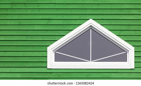 White geometric window on green wood wall. Typical colourful architecture of Iles de la Madeleine in Canada. Space for your text.