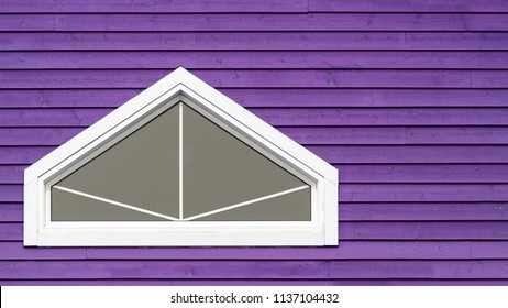White geometric window on purple wood wall. Typical colourful architecture of Iles de la Madeleine in Canada. Space for your text.