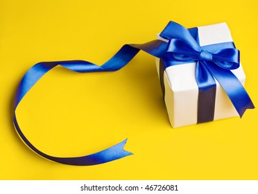 white gift with blue ribbon on a yellow background