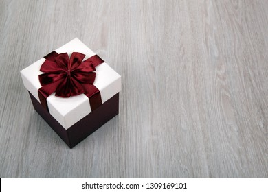 white gift box with a bow on a gray wooden background close up