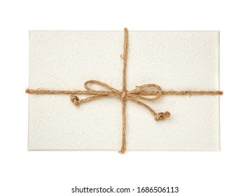 White gift box with burlap ribbon on a white background. Top view.