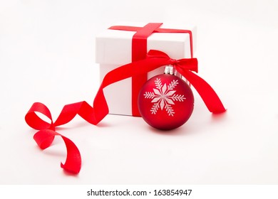 White gift box with curly red ribbon and christmas ball