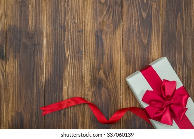 White gift box for holiday event red silk wrap on Wood background isolated