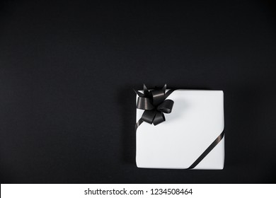 White gift box on a dark contrasted background, decorated with a textured bow, creating a romantic atmosphere. Typically used for birthday, anniversary presents, gift cards, post cards.